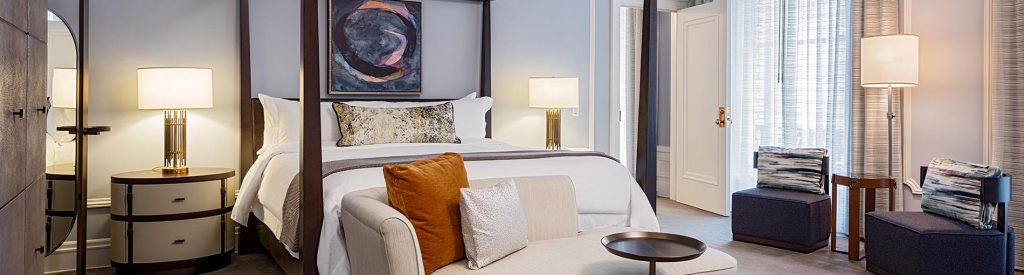 a fancy hotel room featuring custom table and floor lamps